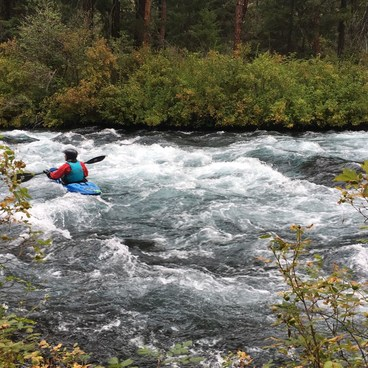 Kayaker heading down the Metolius River--as seen from the trail upriver from Candle Creek.- Candle Creek Campground