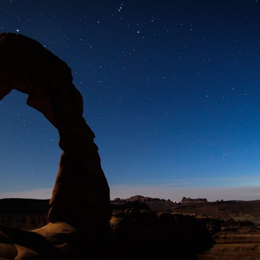 Delicate Arch under the stars while tourists can be seen leaving the park in the distance.- Delicate Arch