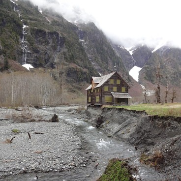 Enchanted Valley Chalet is about to disappear forever!  You can see the corner of the foundation has already fallen into the Quinault River.- Enchanted Valley