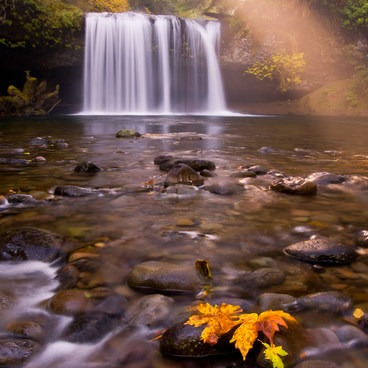 A celestial scene of Upper Butte Creek Falls as a sun beam shines over the falls.- Butte Creek Falls Hike