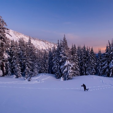 A snowshoer makes tracks as the sun sets- Crater Lake National Park