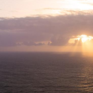 Sun rays burst through a cloud over Tillamook Head Lighthouse- Tillamook Head Hike