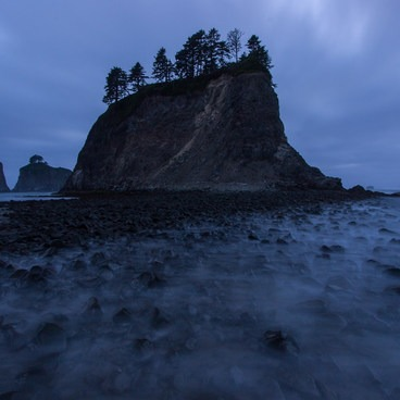 Gentle waves creep in over the sea stacks as the tide moves up- Rialto Beach