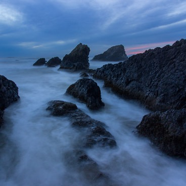 A distant glow appears as the sun sets on a cloudy evening with the tide moving in.- Seal Rock State Recreation Site