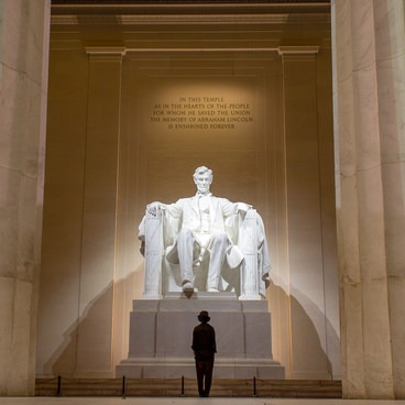 A man peers back at Lincoln in the Lincoln Memorial- National Mall + Memorial Parks