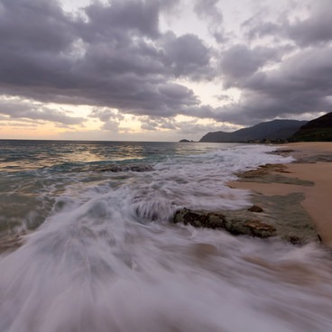 Waves sweep across some rocks in the surf.- Ma'ili Beach Park