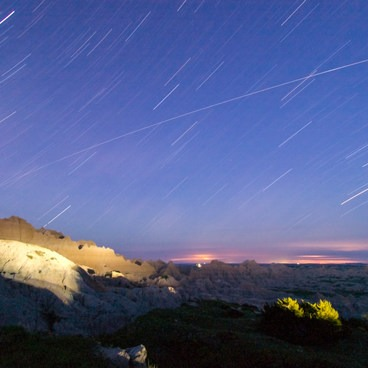 A lightning storm plays out in the distance during a long exposure of star trails- Badlands National Park