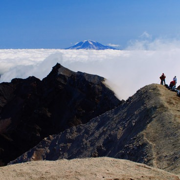 Climbers take a break on the crater rim with Mt Adams above the clouds on the horizon- Mount St. Helens National Volcanic Monument