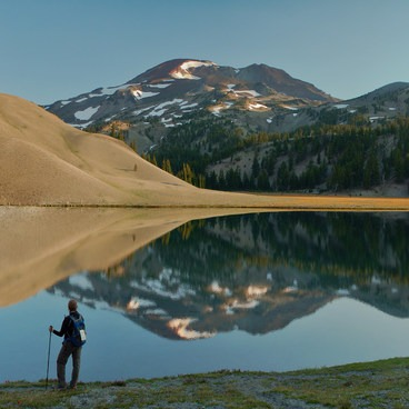 A hiker takes in the view of South Sister reflecting in Moraine Lake- Moraine Lake in the Three Sisters Wilderness