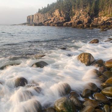 Gentle waves break on the rocky beach below Otter Cliffs- Otter Point + Otter Cliffs