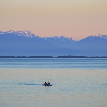 Kayakers on an evening paddle in Haro Strait as seen from the meadow of San Juan Island County Park- San Juan County Day Park + Campground