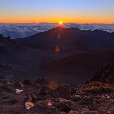 The sun breaks over the horizon and into the valley of Haleakalā- Haleakalā Visitor Center + Pā Ka'oao Trail