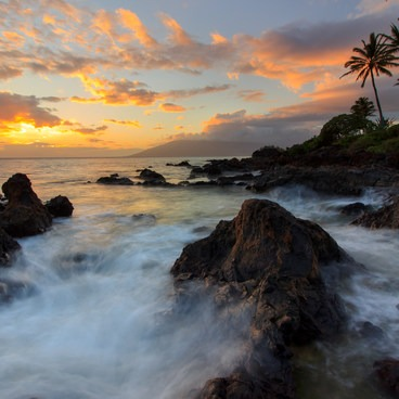 A colorful sunset as waves break apart on the small cove below coastal palms- Kama'ole Beach Park 1 / Charley Young Beach