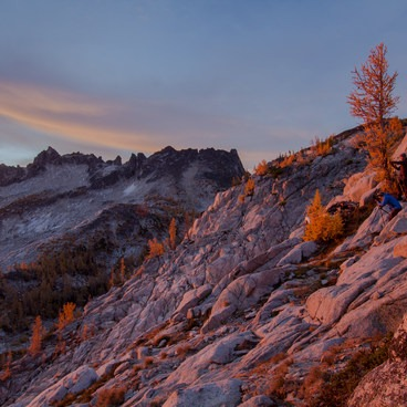 Photographers shoot sunrise from a perch above Perfection Lake with McClellan Peak in the background- Enchantment Lakes Hike via Colchuck Lake