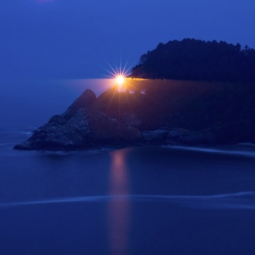 The light shines bright through the foggy evening.- Heceta Head Lighthouse State Scenic Viewpoint