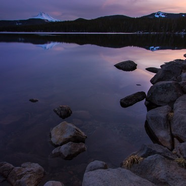 A vibrant sunset over snow-covered Mt Jefferson and the still waters of Olallie Lake- Olallie Lake + Scenic Area
