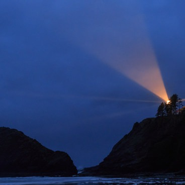 Long exposure of the light through the fog from the beach below.- Heceta Head Lighthouse