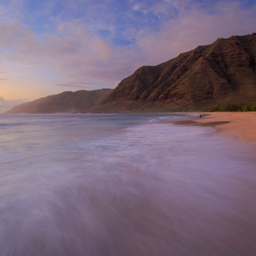 Warm hues bask the area in a glow as a vibrant sunset ends the day over Makua Beach.- Makua Beach