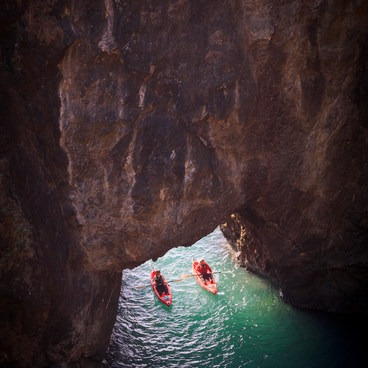 Kayakers paddle through the archway into the cove- Thunder Rock Cove