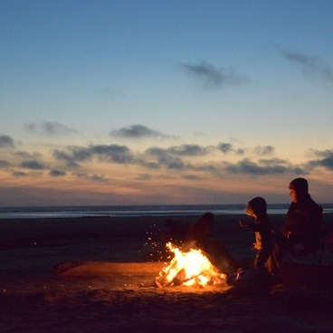A family by a fire on the beach.- Pacific Beach State Park