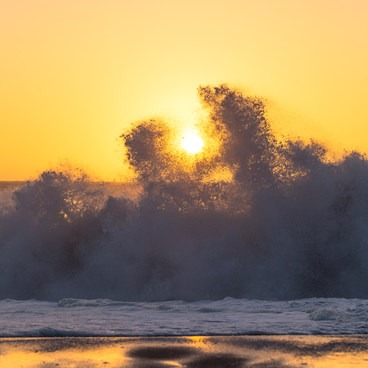 A wave crashes on the beach in front of the sun- Gold Bluffs Beach Campground