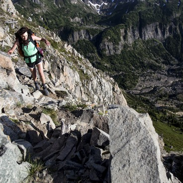 A hiker moves carefully along a narrow, exposed section of the Whittier Ridge Trail- Whittier Ridge Trail from Norway Pass