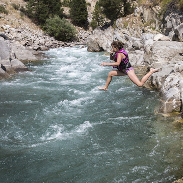 An enthusiastic young hot springs visitor jumps into the Payette river- Kirkham Hot Springs
