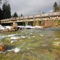 View of the pedestrian bridge over the Breitenbush River.- Breitenbush Hot Springs