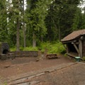 Sleeping shelter and fire pit.- Lost Lake Organization Camp