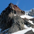Climbers descending in front of Crater Rock in late summer conditions.  Lots of rock and ice fall in the spring, and it's important to keep a heads up while decending  (on the far side of Crater Rock in this photo is Hot Rocks)- Mount Hood South Route: Old Chute