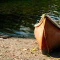 A canoe sits along the edge of the calm water at Squaw Lake.- Squaw Lakes Campground