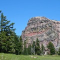The brick-red layers of Dutton Cliff from Sun Notch's pumice meadow.- Sun Notch