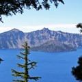 Spy west through the trees to spot Wizard Island across the caldera's lake.- Sun Notch