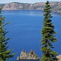 Peek through the trees to find the PhantomShip nestled in Chaski Bay along Crater Lake's East Rim Drive.- Sun Notch