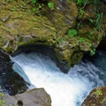 A fenced viewing area overlooks a pothole carved into the riverbed.- Toketee Falls