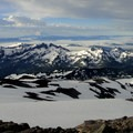 The Tatoosh Range with Goat Rocks and Mount Adams (12,281') on the horizon.- Mount Rainier: Disappointment Cleaver Route