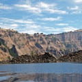 Wizard Island's dark lava flow extends into the Skell Channel (left), creating Fumarole Bay in the foreground. Llao Rock is in the background.- Crater Lake Boat Tour