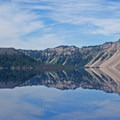 Enjoy ample reflections on the tranquil waters of Crater Lake as your boat proceeds toward Wizard Island.- Crater Lake Boat Tour