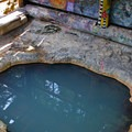 A garden hose sources hot water from the spring beneath the hillside to feed the main pool.- Umpqua Hot Springs
