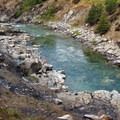 A view over the hot springs nestled along the clear waters of the Payette River.- Kirkham Hot Springs