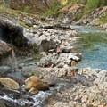 Hot water cascades from above, creating natural showers.- Kirkham Hot Springs