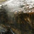 Colorful algae clings to the rocks, drooping over the edges of the ledges above.- Kirkham Hot Springs