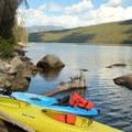 Colorful kayaks parked along the edges of the lake.- Redfish Lake