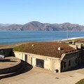 """Battery Chamberlin. The """"disappearing gun"""" installed for demonstration can be seen under cover on the left-most gun platform.- Baker Beach"""