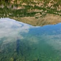Clear blue waters reflect nearby land features.- Washington Lake