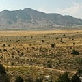 Sagebrush, grasses, and boulders across the wide landscape.- Castle Rocks State Park