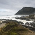 Spouting Horn at Cooks Chasm with Cape Perpetua in the background.- Thor's Well + Cook's Chasm