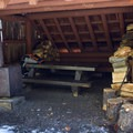 The shelter has a picnic tabel, a woodstove, and a small sleeping platform.- Gold Lake Shelter