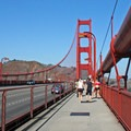 Tourists, cyclists, and joggers fill the bridge's east sidewalk.- Golden Gate Bridge + Fort Point