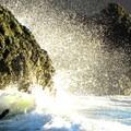 Sunlight through sea spray at College Cove Beach.- College Cove Beach